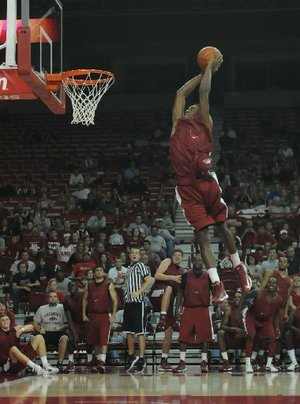 University of Arkansas basketball freshman Michael Qualls flies in the air during a dunking contest at Bud Walton Arena, Friday Oct. 12, 2012, as team mates look on during the Primetime at the Palace.