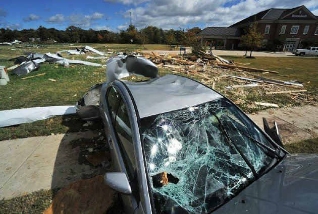 staff-photo-by-michael-woods-10142012-a-car-sits-in-the-debris-from-parts-of-nearby-buildings-that-were-damaged-when-a-suspected-tornado-touched-down-late-saturday-night-in-rogers-along-s-52nd-street-the-storm-damaged-several-building-and-houses-in-the-area-and-caused-damage-to-hundreds-of-trees