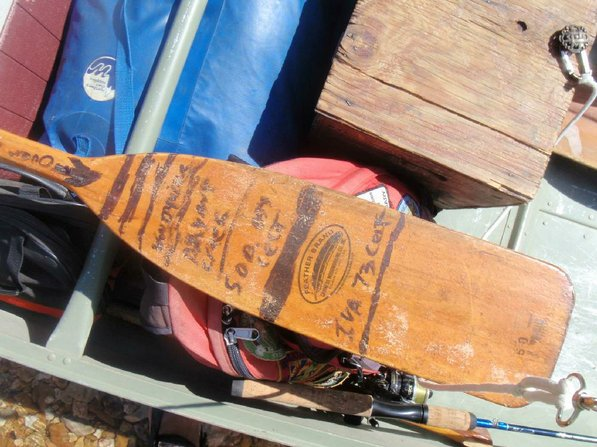 Matt Hughes keeps track of his river trips with notes written in marker on his paddle.