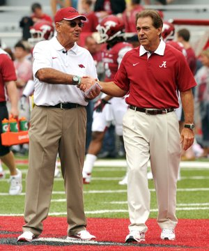 Arkansas Coach John L. Smith (left) meets with Alabama Coach Nick Saban on Sept. 15 in Fayetteville. Smith leads the Razorbacks against Mississippi on Saturday in Little Rock.