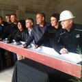 Bentonville school officials sign a beam Friday that will be placed in a new junior high school. The...