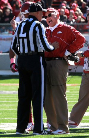 Penalties Arkansas Coach John L. Smith (right) argues with an official about a penalty that cost Arkansas a touchdown in the fourth quarter Saturday. The Razorbacks were penalized 12 times for 70 yards. Ole Miss had five penalties for 33 yards.