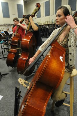 Haley Bowman, right, plays in the bass section with orchestra members Eric Monk, left, and Luke Raihl.