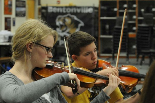 Heidi Dray, left, and Ben Walter play in the violin section of the Bentonville High School orchestra during a practice.