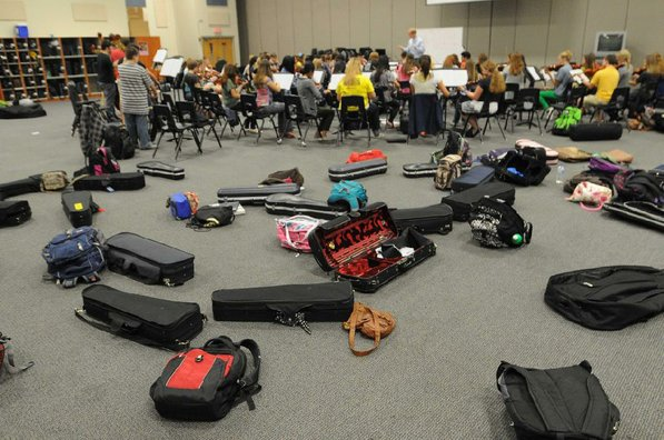 Instrument cases and book packs are standard equipment for orchestra members.