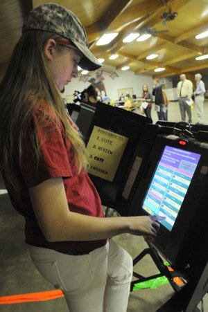 Peggy Sue Standridge votes for the first time Tuesday at the Rodeo of the Ozarks community center in Springdale. Standridge was among 15 Springdale High School seniors who cast their first ballot Tuesday.
