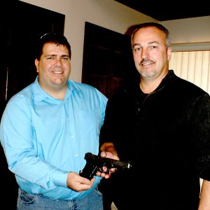 Gravette Mayor Byron Warren surprised retiring Police Chief Trent Morrison by presenting him the Glock 40 semi-automatic pistol which was the officer's first weapon issued him by the Gravette Police Department. It was engraved with Morrison's name and the dates of his service — June 1991-November 2012.