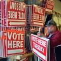 Art Hughes, a poll worker with Washington County's Election Commission, helps load vote signs from t...