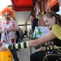 Jake Egberts, left, disguised as a killer clown, moves in for a candy treat Wednesday from queen bee...