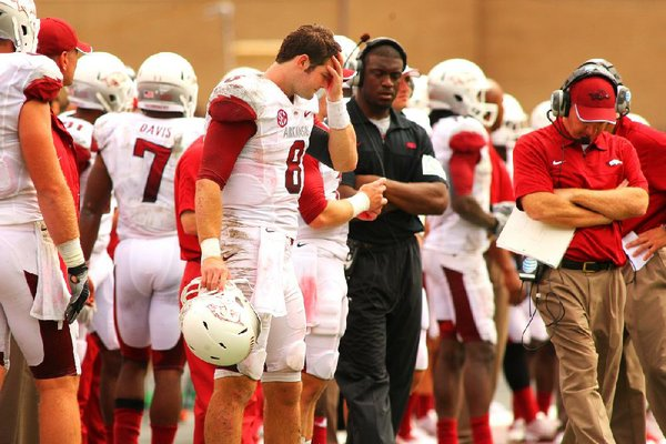 Arkansas quarterback Tyler Wilson (8) and offensive coordinator Paul Petrino (right) lament missed opportunities by the Razorbacks' offense in a 58-10 loss to Texas A&M in September. Arkansas is averaging 27 points a game, its lowest total since 2008.
