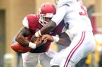 Alabama linebacker C.J. Mosley forces Arkansas running back Knile Davis to fumble in the Crimson Tide's 52-0 victory, one of eight dropped balls by the Hogs in the game.