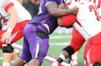 News-Times/Michael Orrell -- El Dorado defensive lineman Bijhon Jackson, purple, works a Camden Fairview offensive lineman in the Wildcats season opener at Memorial Stadium.