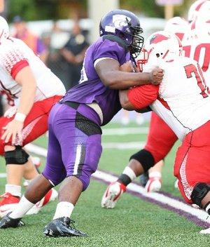 News-Times/Michael Orrell -- El Dorado defensive lineman Bijhon Jackson, purple, works a Camden Fairview offensive lineman in the Wildcats season opener at Memorial Stadium.