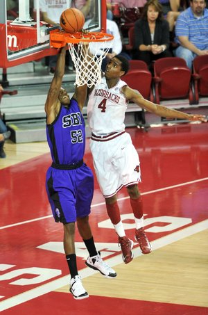 Arkansas forward Coty Clarke (4) blocks a shot by Southwest Baptist forward Jaywuan Hill during the second half of Friday's game at Walton Arena in Fayetteville. Arkansas won 106-78.