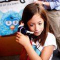 Adrianna Morales, 7, of Bentonville listens closely to a singing One Direction doll Friday during Fi...