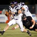 Austin Allen, Fayetteville's senior quarterback, slips past a tackle attempt by Bentonville senior d...
