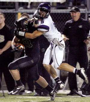 Alex Brignoni, a Fayetteville senior defensive back, brings down Bentonville senior running back Garrett Kaufman during the second half on Friday at Tiger Stadium in Bentonville.