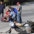 Rhonda Wright, second from left, (above) and Orlando Cabrera assist an injured motorcyclist Friday a...