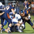 Brandon Gates, right, a Rogers Heritage running back, fights for extra yards while being brought dow...