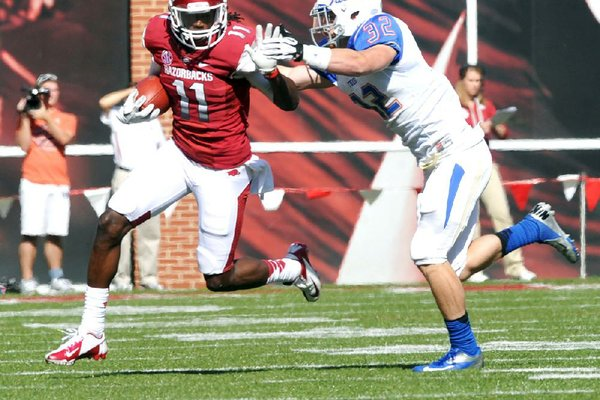 Arkansas receiver Cobi Hamilton (11) tries to fend off Tulsa defender Mitchell Osborne as he runs for 19 yards in the third quarter of Saturday's game at Reynolds Razorback Stadium in Fayetteville.