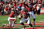 Running back Dennis Johnson (33) scores Arkansas' first touchdown, an 8-yard run in the first quarter, as tight end Alex Voelzke (46) and wide receiver Javontee Herndon (19) celebrate. Johnson, who rushed for 109 yards on 22 carries, also scored Arkansas' final touchdown from a yard out to seal the 19-15 victory over Tulsa. Johnson, a fifth-year senior from Texarkana, has consecutive 100-yard games for the first time as a Razorback.