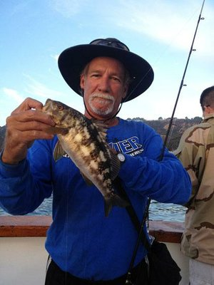 Jack Slemp of San Diego, an assistant on a charter boat that operates from a marina in San Diego Harbor, shows off a calico bass he caught near the mouth of the bay.