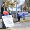Joel Keller, from left, Mike Carney and Jim Murawski hold political signs Thursday outside of an ear...