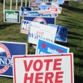 "A ""Vote Here"" sign is mixed in with all the political signs at the entrance to Parsons Stadium on Th..."
