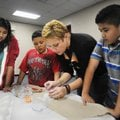 Jeanette Arnhart, a student at the University of Arkansas, shows students at J.O. Kelly Middle Schoo...