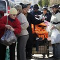 Residents line up for bundles of food at an American Red Cross station in the Coney Island section o...