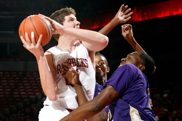 Arkansas sophomore Hunter Mickelson shoots over LeMoyne-Owen's Edwin Shorter during the first half of Monday's exhibition game. Mickelson had nine points and the Razorbacks won 111-45.