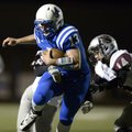 Nick Wary, Rogers High quarterback, carries the ball on a keeper play Oct. 26 during the game agains...
