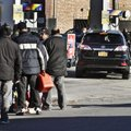 Police direct cars to pumps while people stand in line with containers for gas on Friday, Nov. 9, 20...