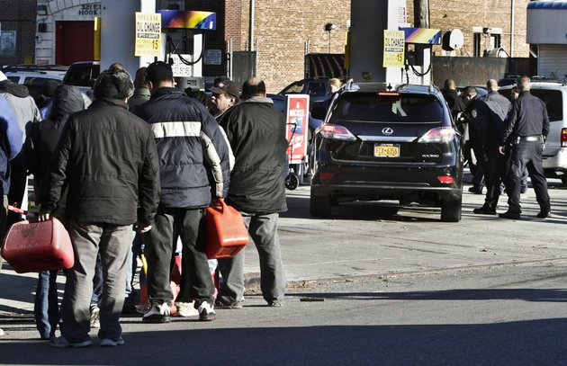 police-direct-cars-to-pumps-while-people-stand-in-line-with-containers-for-gas-on-friday-nov-9-2012-in-the-brooklyn-borough-of-new-york-police-were-at-gas-stations-to-enforce-a-new-gasoline-rationing-plan-that-lets-motorists-fill-up-every-other-day