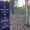 A sign indicates the multiple trail routes visitors can take to an entrance at Crystal Bridges Museu...