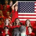 Sixth-grader Brooklyn Dostie helps hold an American flag Friday during the Veterans Day Concert at O...