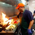Oscar Garcia grills fish in the kitchen Friday during lunch at the Flying Fish restaurant in downtow...