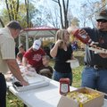 Cody Anglin of Bentonville enjoys a free hot dog lunch Saturday at the dedication of the new Austin-...