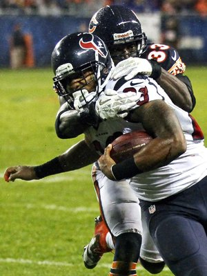 Houston running back Arian Foster is tackled by Chicago cornerback Charles Tillman on Sunday night in Chicago.