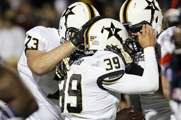 Vanderbilt kicker Carey Spear (39) receives congratulatory helmet slaps from his teammates, including Chase White (73), after kicking the winning extra point in the fourth quarter of an NCAA college football game against Mississippi in Oxford, Miss., Saturday, Nov. 10, 2012. Vanderbilt won 27-26. (AP Photo/Rogelio V. Solis)