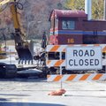 Construction crews work on leveling a railroad crossing Tuesday at Cato Springs Road in Fayetteville...