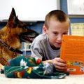 Third-grader Lucas Berens (above) reads Tuesday while laying next to Maxie, a 10-year-old German she...