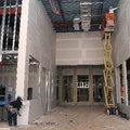 Construction crews from Built-Well Construction in Bentonville add drywall Tuesday to the entrance o...