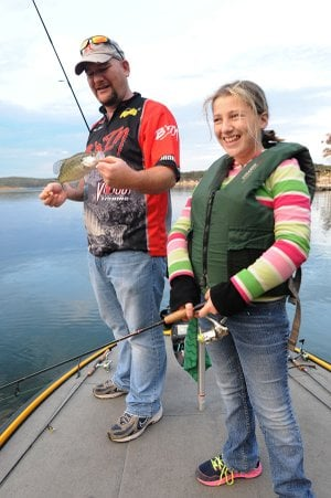Katelyn Piper and her dad, fishing guide Jason Piper of Rogers, work jigs around timber for crappie Friday in the Horseshoe Bend area of Beaver Lake. Fishing has been good this fall around timber and docks, the Piper team said.