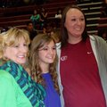 Anna Holcomb, center, a Springdale High volleyball player, stands with Springdale volunteer assistan...