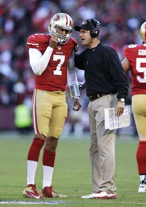 "San Francisco 49ers Coach Jim Harbaugh (right) speaks with quarterback Colin Kaepernick during Sunday's game. Harbaugh was hospitalized Thursday for a ""minor procedure."""