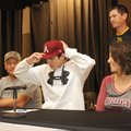 Aaron Kincaid, center, Prairie Grove senior, signs Thursday to play baseball for the University of A...