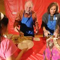 Dick and Julie Johnson of Fayetteville serve a Thanksgiving dinner to visitors Thursday at the Donal...