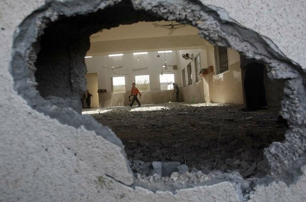 a-palestinian-child-walks-through-a-damaged-mosque-after-an-israeli-airstrike-in-beit-hanoun-northern-gaza-friday-nov-16-2012