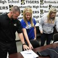 Kent Early, head coach, from left, shows Anna Thomas and Kate Lacina, softball players from Bentonvi...